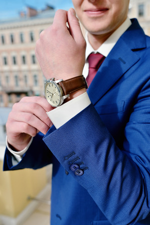 Groom is wearing a wrist watch indoors. Male portrait of handsome guy. Beautiful model boy in colorful wedding clothes. Man is posing