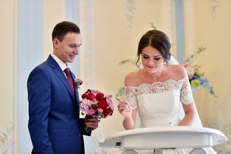 marrying: Beauty bride and handsome groom are registering the marriage. Wedding couple is marrying. Beautiful model girl in white dress and in lace veil. Man in suit. Female and male portrait. Cute lady and guy