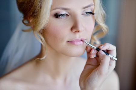 신부를 위해 메이크업을하는 웨딩 메이크업 아티스트. 아름 다운 섹시 한 모델 소녀 실내입니다. 곱슬 머리를 가진 아름다움 여자입니다. 여성 초상화 스톡 콘텐츠
