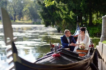 cute guy: Wedding couple is hugging on a floating gondola. Beauty bride with groom. Beautiful model girl in white dress. Man in suit. Female and male portrait. Woman with lace veil. Cute lady and guy outdoors