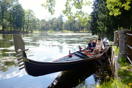 Wedding couple is hugging on a floating gondola. Beauty bride with groom. Beautiful model girl in white dress. Man in suit. Female and male portrait. Woman with lace veil. Cute lady and guy outdoors
