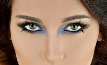 makeup eyes: Portrait of sexy fashion model girl with perfect bright makeup. Beautiful woman with long false eyelashes. Close up of eyes with blue and purple color shadows. Closeup shiny face of a young white girl