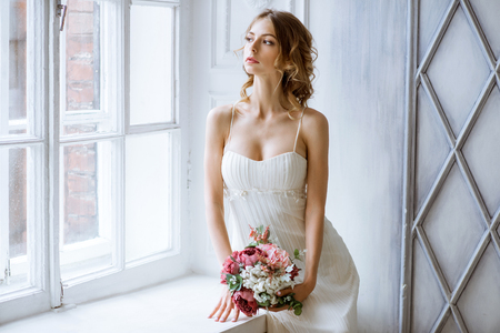 Brunette bride in fashion white wedding dress with makeup Stock Photo
