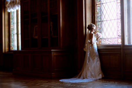 e9116272d9a Beauty bride in bridal gown with bouquet and lace veil indoors