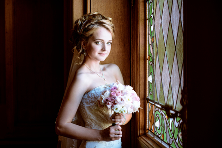 Beauty bride in bridal gown with bouquet and lace veil indoors