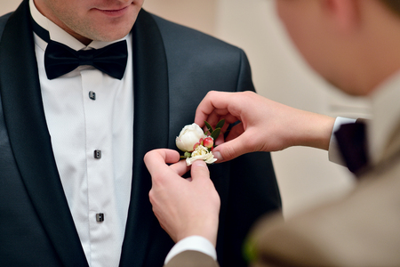 cuff link: Groom is wearing a suit indoors