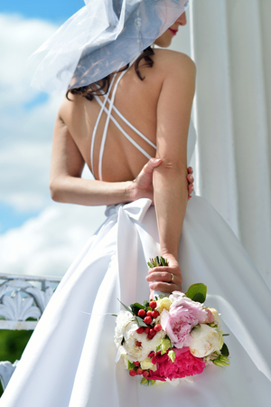 Beauty bride in bridal gown with bouquet and lace veil in the nature Фото со стока