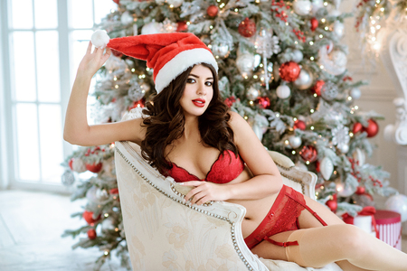 Beautiful brunette sexy Santa Clause in elegant panties, hat and bra