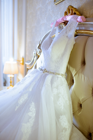 Beautiful white wedding dress for bride indoors on the bed