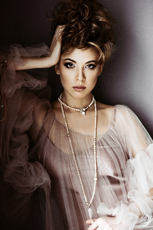 Fashionable female portrait of cute lady in pink dress indoors Foto de archivo