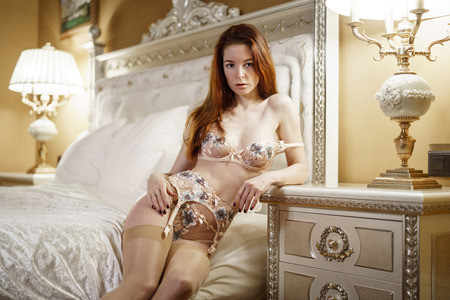 Beautiful sexy lady in white panties and bra on the bed Foto de archivo