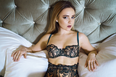 Beautiful sexy lady in green panties and bra on a bed
