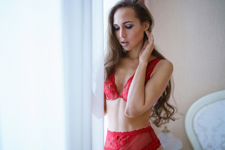 Beautiful sexy lady in red panties and bra in the bedroom Stock Photo