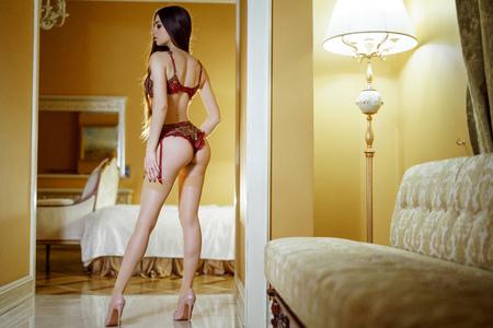 Beautiful sexy lady in red panties and bra in bedroom Foto de archivo