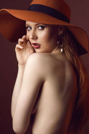 Fashionable female portrait of cute lady indoors with hat. Close up beautiful sexy model girl in elegant pose isolated on brown background. Closeup beauty blonde woman with hairstyle and makeup Standard-Bild