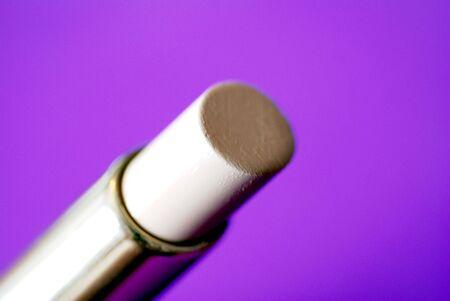 concealer: Un tubo di cosmetici concealer contro un sfondo viola