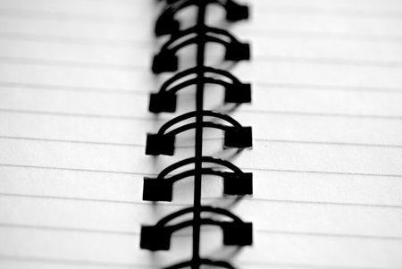 A spiral-bound notepad close-up in black and white photo