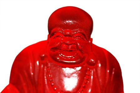 A statue of the Laughing Buddha made out of red glass, isolated on a white background. photo