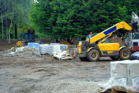 heavy machinery: A photograph of a building site with numerous examples of heavy machinery.
