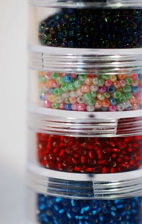 seed pots: A close up photograph of four pots of seed beads for craft