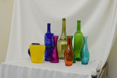 still life of colored bottles on a white background