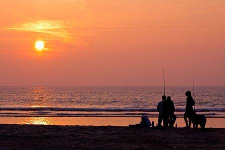 Fishermen on the beach at sunset