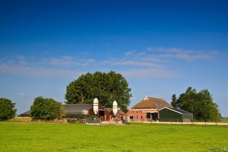 Countryside with farm on a green grassland photo