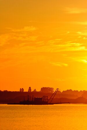Dredger vessel working in the early morning at sunset photo