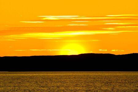 Beautiful orange Sunset behind the hills near water photo