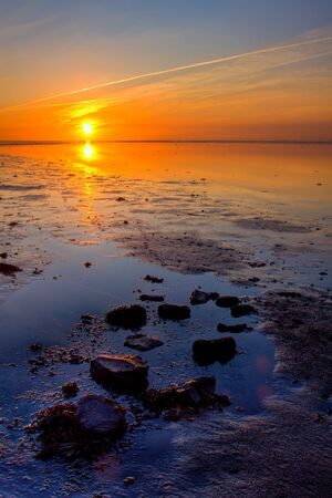 Colorful sunrise at the wadden sea coastline