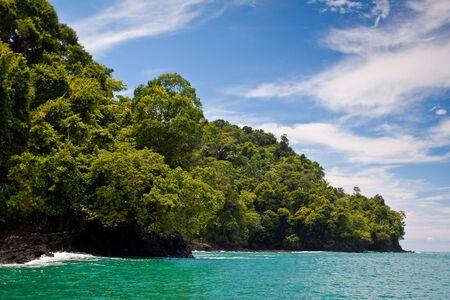 Rocky coastline and jungle near the sea with blue sky Stock Photo