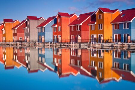 Colorful wooden houses near water in the morning sun Standard-Bild