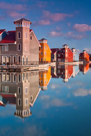 Colorful wooden houses near water in the morning sun Stock Photo