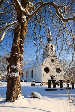 churchyard: Tree and church in a cold white winter landscape Stock Photo