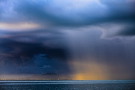 Thunder storm with rain lit by the sun at a lake