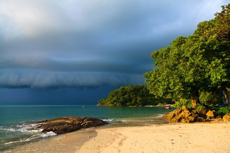 Thunder storm approaching the tropical beach lit by sun