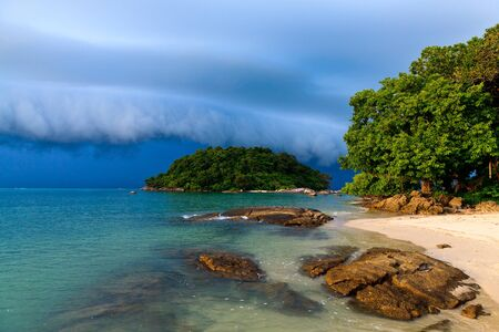 Thunder storm approaching the tropical beach lit by sun photo