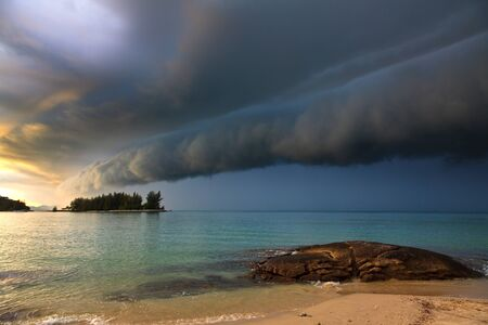 Thunder storm with roll cloud approaching the tropical beach photo