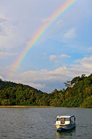 Colorfull rainbow over a tropical beach with forest photo