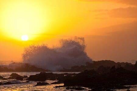 High wave breaking on the rocks at sunset Stock Photo - 11409126