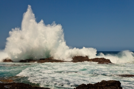 High wave breaking on the rocks of the coastline photo