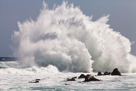rompiendo: De onda de alta de �ltima hora en las rocas de la costa Foto de archivo