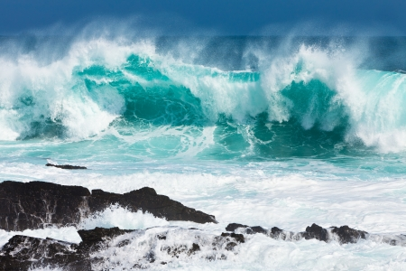 huge: Turquoise rolling wave slaming on the rocks of the coastline Stock Photo