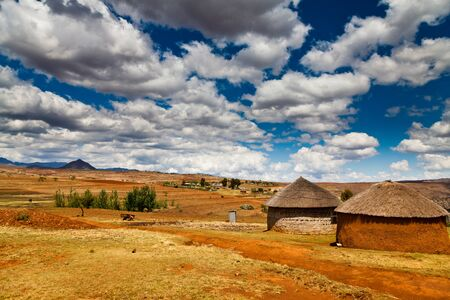 Village in a valley in africa with beautiful cloudscape photo