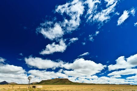 mill valley: Windmill in a desolate landscape with beautiful cloudscape in Africa Stock Photo