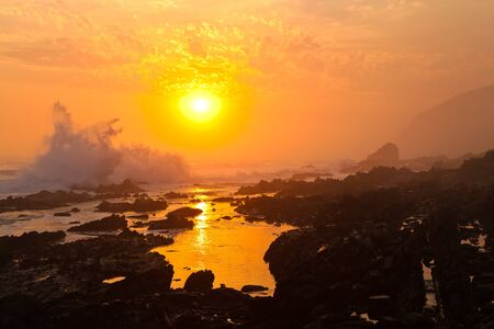 High wave breaking on the rocks at sunset Stock Photo - 13290732