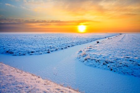 Grassland with ditch in winter at sunset photo