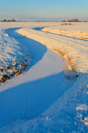 Winter landscpae of a ditch at sunset photo