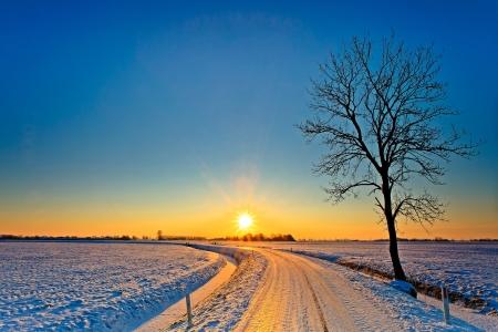 Puesta de sol en un paisaje de invierno blanco y frío Foto de archivo