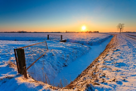 Sunset and fence with grassland in winter time photo